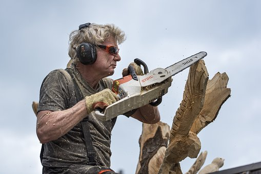 old man using a chain saw